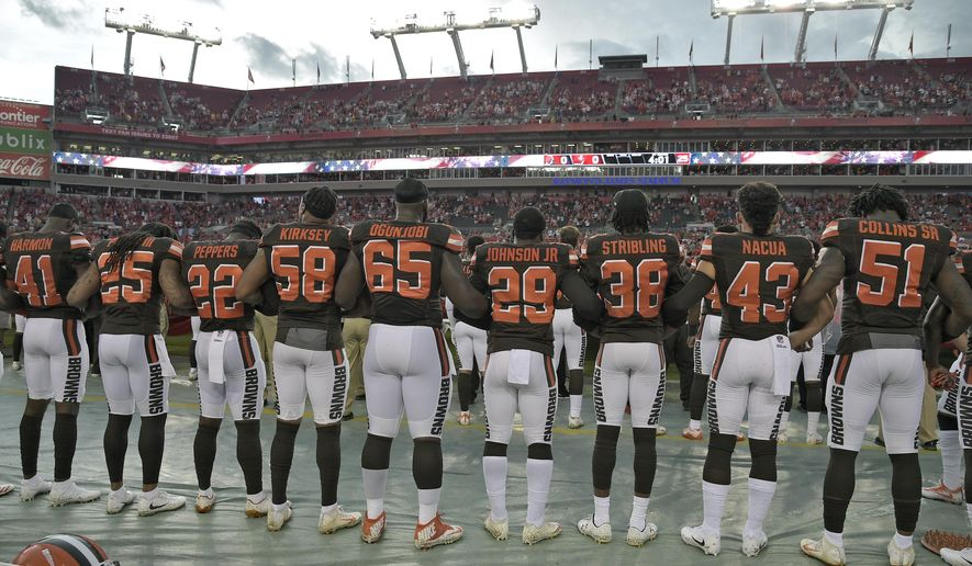 Cleveland Browns players lock arms during the playing of the national anthem before an NFL preseason football game against the Tampa Bay Buccaneers Saturday, Aug. 26, 2017, in Tampa, Fla. (AP Photo/Phelan M. Ebenhack)