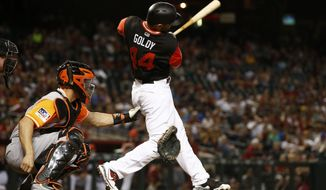 Arizona Diamondbacks' Paul Goldschmidt (44) follows through on a single after knocking the glove off of San Francisco Giants catcher Nick Hundley, left, during the first inning of a baseball game Friday, Aug. 25, 2017, in Phoenix. (AP Photo/Ross D. Franklin)