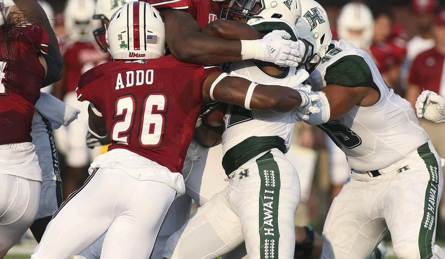 Massachusetts' Ali Ali-Musa, top, and Jerall Addo (26) take down Hawaii's Mykal Tolliver during the first quarter of an NCAA college football game Saturday, Aug. 26, 2017, in Amherst, Mass. (J. Anthony Roberts/The Republican via AP)