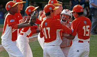 Texas catcher Chandler Spencer, second from right, begins to celebrate with Mark Requena (15) and Collin Ross (17) after getting the final out of a 6-5 win over North Carolina in the United States Championship baseball game at the Little League World Series tournament in South Williamsport, Pa., Saturday, Aug. 26, 2017. (AP Photo/Gene J. Puskar)