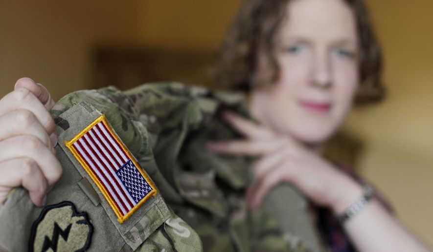 In this July 29, 2017, file photo transgender U.S. Army Capt. Jennifer Sims lifts her uniform during an interview with The Associated Press in Beratzhausen near Regensburg, Germany. (AP Photo/Matthias Schrader) ** FILE **