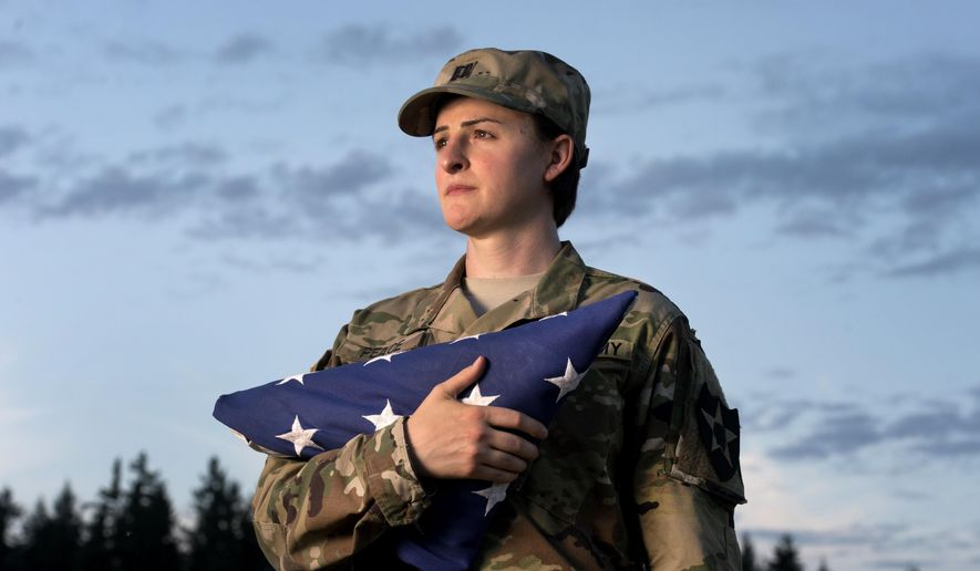 In this Aug. 28, 2015, file photo, Capt. Jennifer Peace, who is transgender, holds a flag as she stands for a photo near her home in Spanaway, Washington. The Obama administration lifted a ban on transgender service in the military, but the Trump administration reversed that policy. A bill that passed that U.S. House of Representatives July 31 would rescind the Trump Pentagon's transgender ban. (Drew Perine/The News Tribune via AP, File )  **FILE**