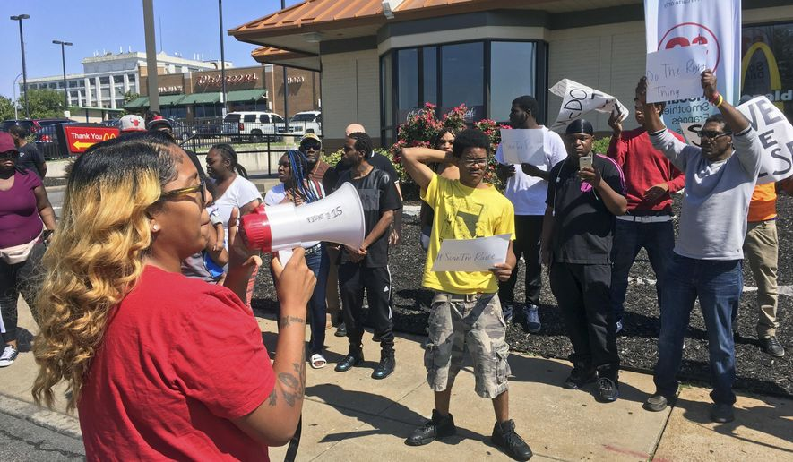 "In this Thursday, Aug. 24, 2017, photo, Gennice Mackey uses a bullhorn to lead a chant of ""Save the Raise!"" outside a McDonald's restaurant in St. Louis. A Missouri law that takes effect Monday, Aug. 28, prohibits cities from having a higher minimum wage than the state's wage of $7.70 per hour. That means St. Louis' $10 minimum wage will be rolled back. But advocates of a higher wage are urging employers to keep the $10 minimum wage. (AP Photo/Jim Salter)"