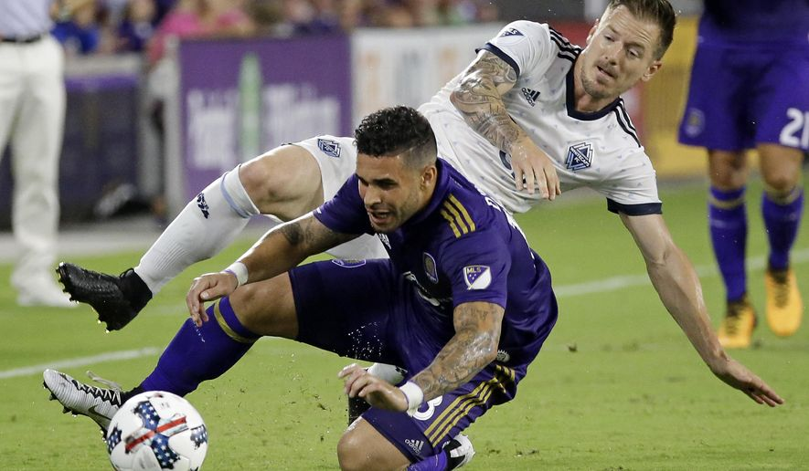 Orlando City 's Dom Dwyer, front, gets tangled up with Vancouver Whitecaps's Jordan Harvey while going for the ball during the first half of an MLS soccer match, Saturday, Aug. 26, 2017, in Orlando, Fla. (AP Photo/John Raoux)