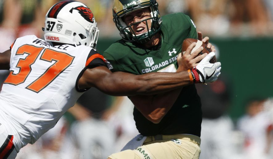 Oregon State linebacker Kee Whetzel, left, tries to tackle Colorado State quarterback Nick Stevens as he looks to pass the ball in the second half of an NCAA college football game Saturday, Aug. 26, 2017, in Fort Collins, Colo. (AP Photo/David Zalubowski)