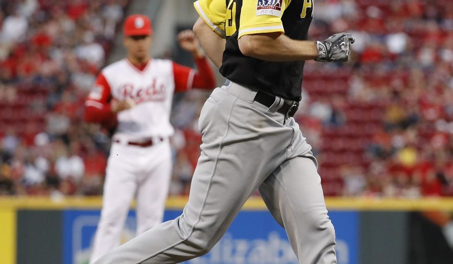 Pittsburgh Pirates' Gerrit Cole runs the bases after hitting a solo home run off Cincinnati Reds starting pitcher Luis Castillo, left, during the sixth inning of a baseball game, Saturday, Aug. 26, 2017, in Cincinnati. (AP Photo/John Minchillo)