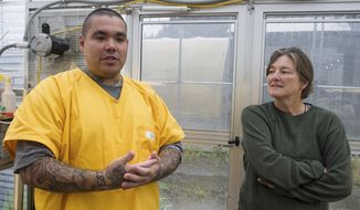 Inmate David Guthrie, left, talks about growing peppers with Education Coordinator Kris Weixelman at the Lemon Creek Correctional Center in Juneau, Alaska, on Wednesday, Aug. 16, 2017. In a twist on the popular farm to table movement that has swept the country, with restaurants and cities promoting ways to bring fresh-from-the-dirt produce directly to consumers, state prisons are experimenting with ways to bring produce grown by inmates to their own kitchens and even out into the community. (Michael Penn/Juneau Empire via AP)