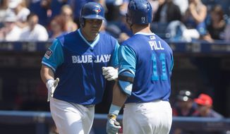 Toronto Blue Jays' Kendrys Morales, left, is congratulated by teammate Kevin Pillar after hitting a solo home run against the Minnesota Twins during second inning American League MLB baseball action in Toronto on Saturday, Aug. 26 2017. (Chris Young/The Canadian Press via AP)