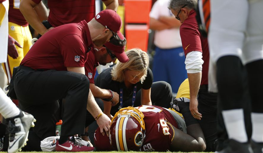 Washington Redskins defensive tackle Phillip Taylor (99) is tended to after a play in the first half of a preseason NFL football game against the Cincinnati Bengals, Sunday, Aug. 27, 2017, in Landover, Md. (AP Photo/Alex Brandon)