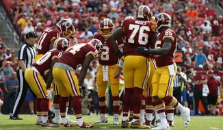 Washington Redskins quarterback Kirk Cousins (8) huddles with teammates in the first half of a preseason NFL football game against the Cincinnati Bengals, Sunday, Aug. 27, 2017, in Landover, Md. (AP Photo/Alex Brandon)