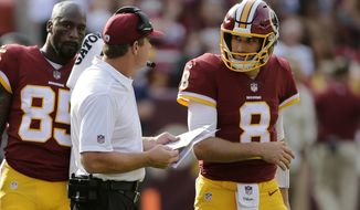 Washington Redskins quarterback Kirk Cousins, right, speaks with head coach Jay Gruden in the first half of a preseason NFL football game against the Cincinnati Bengals, Sunday, Aug. 27, 2017, in Landover, Md. (AP Photo/Mark Tenally)