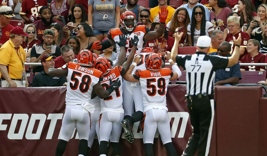 Cincinnati Bengals outside linebacker Vontaze Burfict, top, celebrates with teammates after intercepting a pass by Washington Redskins quarterback Kirk Cousins and scoring a touchdown in the first half of a preseason NFL football game, Sunday, Aug. 27, 2017, in Landover, Md. (AP Photo/Alex Brandon)