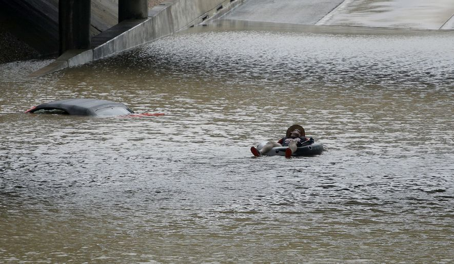 A man floats past a stalled car submerged on a freeway flooded by Tropical Storm Harvey on Sunday, Aug. 27, 2017, near downtown Houston. The remnants of Hurricane Harvey sent devastating floods pouring into Houston Sunday as rising water chased thousands of people to rooftops or higher ground. (AP Photo/Charlie Riedel)