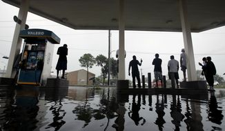 People watch heavy rain from the relative safety of a flooded gas station caused by Tropical Storm Harvey on Sunday, Aug. 27, 2017, in Houston. The remnants of Hurricane Harvey sent devastating floods pouring into Houston Sunday as rising water chased thousands of people to rooftops or higher ground. (AP Photo/Charlie Riedel)