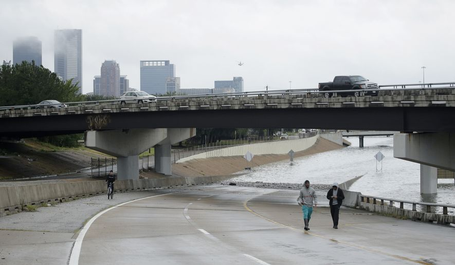 People walk on freeway flooded by Tropical Storm Harvey on Sunday, Aug. 27, 2017, near downtown Houston, Texas. (AP Photo/Charlie Riedel)