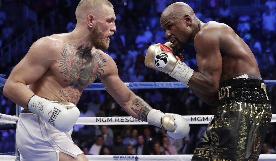 Floyd Mayweather Jr., right, fights Conor McGregor in a super welterweight boxing match Saturday, Aug. 26, 2017, in Las Vegas. (AP Photo/Isaac Brekken)