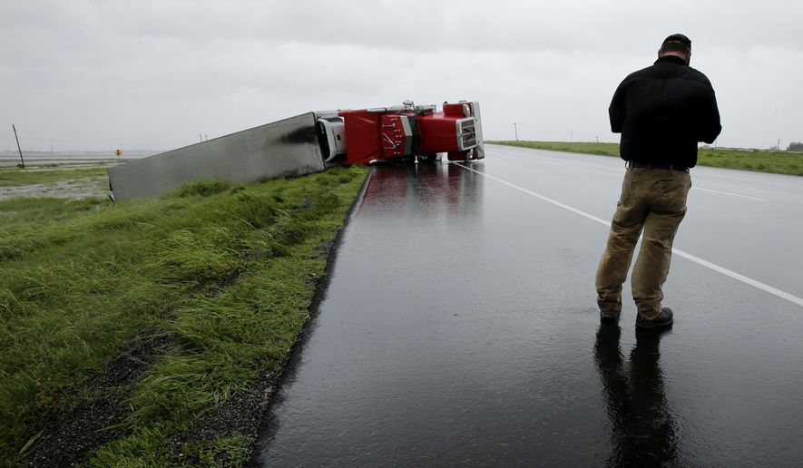 A passing motorist stops to look at a flipped truck in the aftermath of Hurricane Harvey Saturday, Aug. 26, 2017, north of Victoria, Texas. (AP Photo/Charlie Riedel)