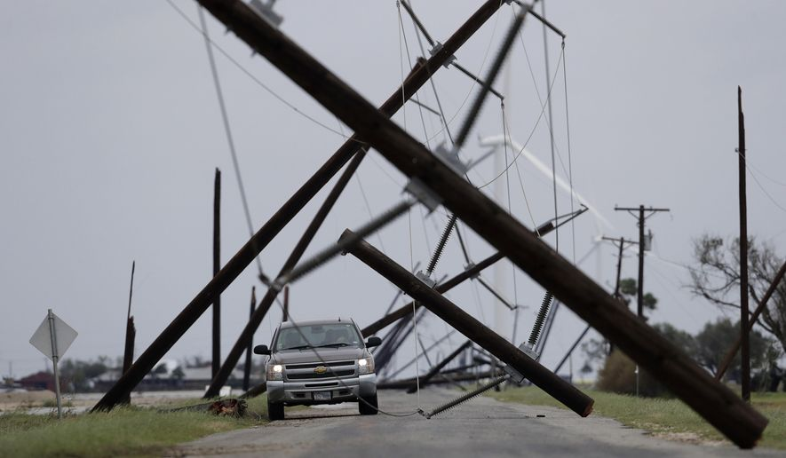 A driver works his way through a maze of fallen utility poles damaged in the wake of Hurricane Harvey, Saturday, Aug. 26, 2017, in Taft, Texas. (AP Photo/Eric Gay)