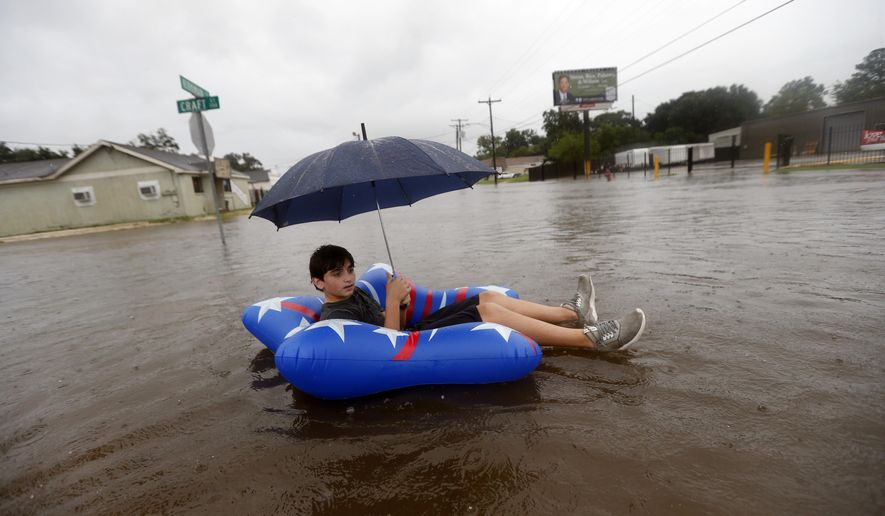Julius Verret, 14, floats in street flooding in Lake Charles, La., as the city is receiving heavy rains from Tropical Storm Harvey, Sunday, Aug. 27, 2017. The storm came ashore on the Texas Gulf Coast as a category four hurricane. (AP Photo/Gerald Herbert)