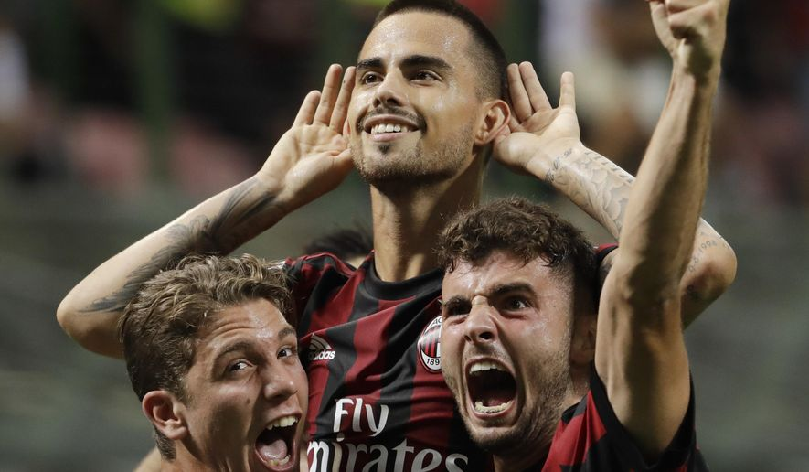 AC Milan's Suso, top, celebrates with teammates Patrick Cutrone, right, and Manuel Locatelli after scoring, during a Serie A soccer match between AC Milan and Cagliari, at the San Siro stadium in Milan, Italy, Sunday, Aug. 27, 2017. (AP Photo/Luca Bruno)