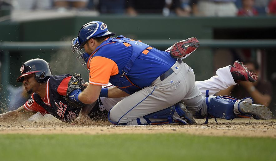 Washington Nationals' Edwin Jackson, back, is out at home plate by New York Mets catcher Travis d'Arnaud, front, during the ninth inning of the first baseball game of a split doubleheader, Sunday, Aug. 27, 2017, in Washington. (AP Photo/Nick Wass)