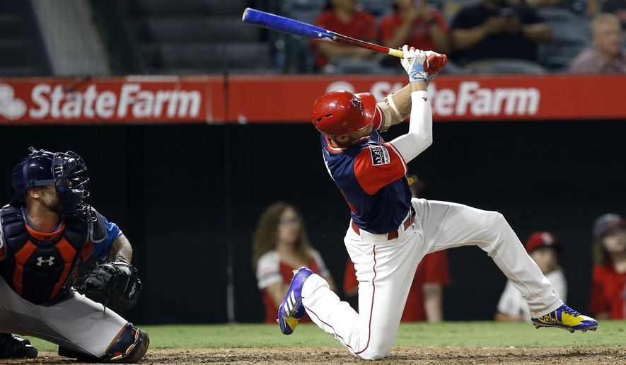 Los Angeles Angels' Andrelton Simmons, right, follows through on a three-run home run with Houston Astros catcher Brian McCann watching during the eighth inning of a baseball game in Anaheim, Calif., Saturday, Aug. 26, 2017. (AP Photo/Alex Gallardo)