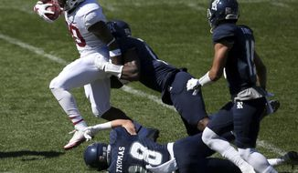 Stanford's running back Bryce Love, left, breaks tackles as he runs against the Rice defence during the opening game of the U.S. college football season in Sydney, Sunday Aug. 27, 2017. (AP Photo/Rick Rycroft)
