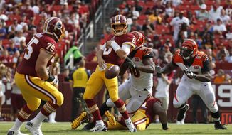 Washington Redskins quarterback Kirk Cousins, center, throws as he is tackled by Cincinnati Bengals defensive end Michael Johnson (90) in the first half of a preseason NFL football game, Sunday, Aug. 27, 2017, in Landover, Md. Cousins received an intentional grounding penalty on the play. (AP Photo/Alex Brandon)