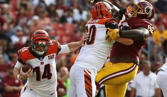 Cincinnati Bengals quarterback Andy Dalton (14) rushes the ball as Cincinnati Bengals center T.J. Johnson holds back Washington Redskins defensive tackle Stacy McGee in the first half of a preseason NFL football game, Sunday, Aug. 27, 2017, in Landover, Md. (AP Photo/Alex Brandon)