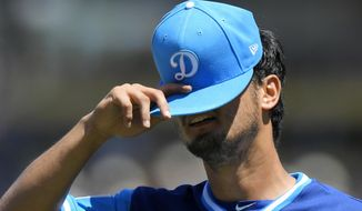 Los Angeles Dodgers starting pitcher Yu Darvish, of Japan, puts his cap back on after wiping his face following the first inning of a baseball game against the Milwaukee Brewers, Sunday, Aug. 27, 2017, in Los Angeles. (AP Photo/Mark J. Terrill)