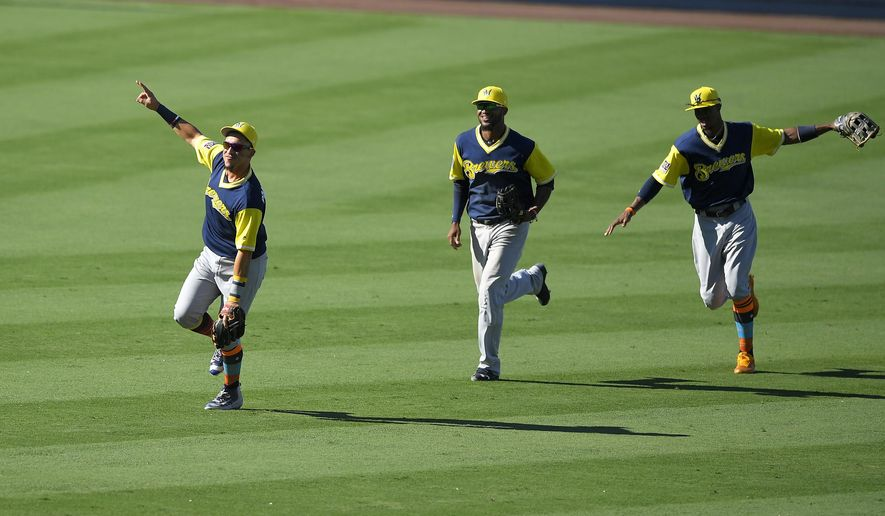 Milwaukee Brewers' Hernan Perez, left, Domingo Santana, center, and Keon Broxton celebrate after they defeated the Los Angeles Dodgers in a baseball game, Sunday, Aug. 27, 2017, in Los Angeles. (AP Photo/Mark J. Terrill)
