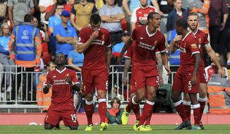 Liverpool's Sadio Mane, left, celebrates scoring his side's second goal of the game against Arsenal during their English Premier League soccer match at Anfield, Liverpool, England, Sunday, Aug. 27, 2017. (Peter Byrne/PA via AP)