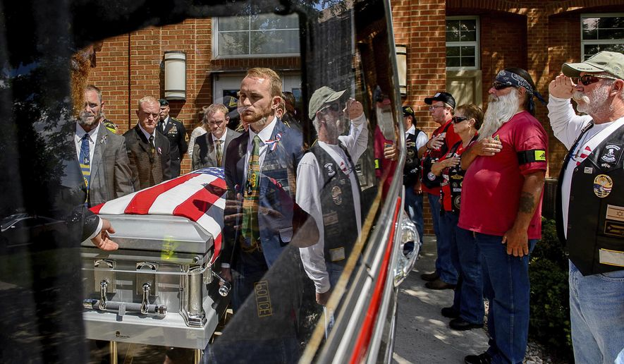 Mourners offer signs of respect as pallbearers carry the casket of fallen solider Aaron Butler, who was killed in action in Afghanistan earlier in the month, at the funeral in Monticello, Utah, Saturday, Aug. 26, 2017. (Trent Nelson/The Salt Lake Tribune via AP)