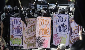 """Demonstrators hold shields during a free speech rally Sunday, Aug. 27, 2017, in Berkeley, Calif. Several thousand people converged in Berkeley Sunday for a """"Rally Against Hate"""" in response to a planned right-wing protest that raised concerns of violence and triggered a massive police presence. Several people were arrested for violating rules against covering their faces or carrying items banned by authorities. (AP Photo/Marcio Jose Sanchez)"""