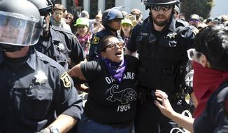 "A demonstrator is arrested during a free speech rally Sunday, Aug. 27, 2017, in Berkeley, Calif. Several thousand people converged in Berkeley Sunday for a ""Rally Against Hate"" in response to a planned right-wing protest that raised concerns of violence and triggered a massive police presence. Several people were arrested for violating rules against covering their faces or carrying items banned by authorities. (AP Photo/Josh Edelson)"