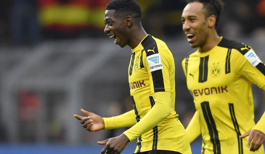 FILE - In this Feb. 18, 2017 file photo Borussia Dortmund's Ousmane Dembele of France, left, celebrates beside teammate Pierre-Emerick Aubameyang during the Bundesliga soccer match against VfL Wolfsburg in Dortmund, Germany. Borussia Dortmund's CEO Hans-Joachim Watzke said at the annual balance press conference Friday, Aug. 25, 2017 that he is optimistic about the record transfer of the 20-year-old Ousmane Dembele to FC Barcelona very soon. (AP Photo/Martin Meissner, file)