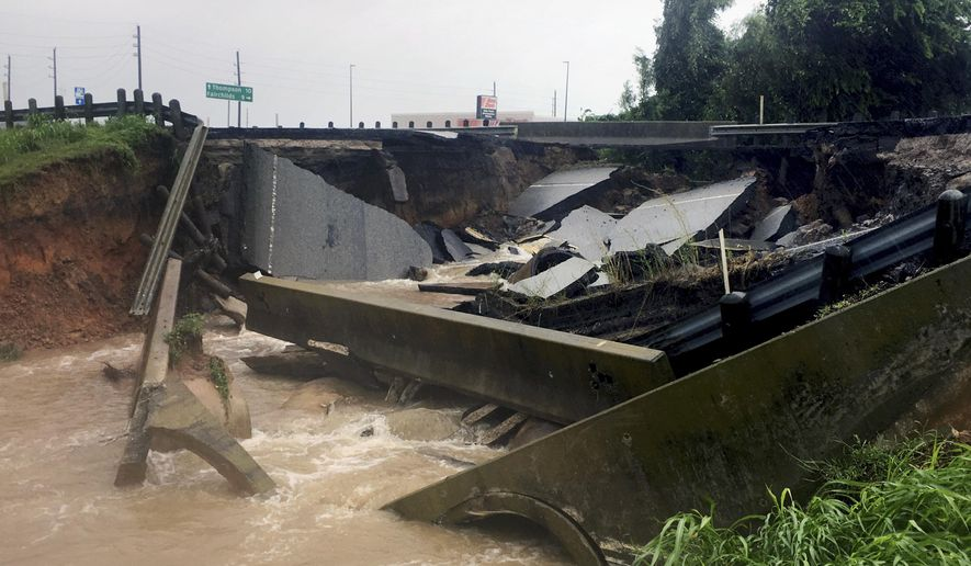 Waters rush from a large sinkhole on Highway FM 762 in Rosenberg, Texas, near Houston, Sunday, Aug. 27, 2017. Police say the sinkhole has opened on the Texas highway as Tropical Storm Harvey dumps more rain on the region. (AP Photo/John Mone)
