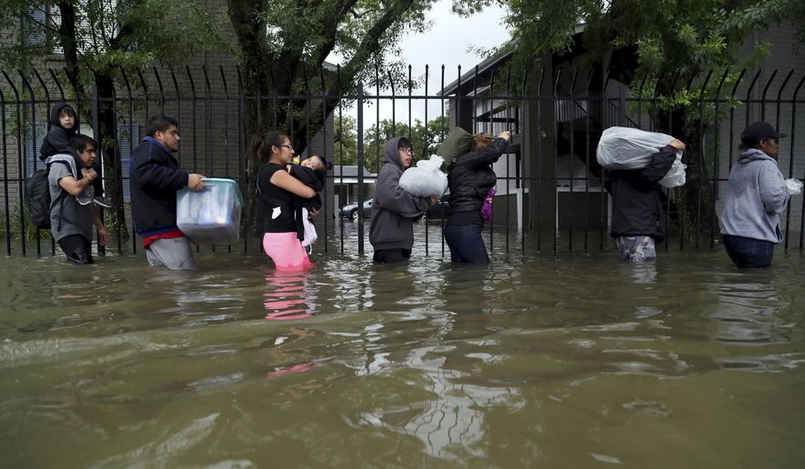 Residents from Bayou Parc at Oak Forest carry their belongings while evacuating the apartment complex during the Tropical Storm Harvey, Sunday, Aug. 27, 2017, in Houston.  The remnants of Hurricane Harvey sent devastating floods pouring into Houston Sunday as rising water chased thousands of people to rooftops or higher ground. (Marie D. De Jesus/Houston Chronicle via AP)