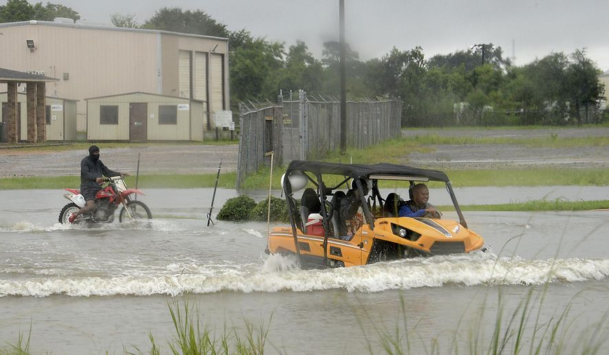 While Cardinal Drive was impassable for vehicles, it made for a sport outing for some in their all terrain vehicles and motor bikes Sunday, Aug. 27, 2017, after Harvey's heavy rain bands moved into the area. (Kim Brent/The Beaumont Enterprise via AP)