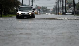 Cars drive through flooded streets in Lake Charles, La., as the city is receiving heavy rains from Tropical Storm Harvey, Sunday, Aug. 27, 2017. The storm came ashore on the Texas Gulf Coast as a category four hurricane. (AP Photo/Gerald Herbert)