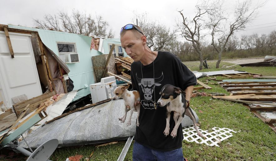 Sam Speights holds two of his dogs as he checks on the damage to his home in the wake of Hurricane Harvey, Sunday, Aug. 27, 2017, in Rockport, Texas. Speights tried to stay in his home during the storm but had to move to other shelter after his lost his roof and back wall. (AP Photo/Eric Gay)