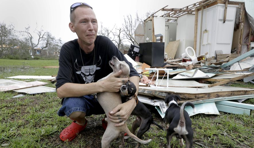 Sam Speights tries to hold back tears while holding his dogs and surveying the damage to his home in the wake of Hurricane Harvey, Sunday, Aug. 27, 2017, in Rockport, Texas. Speights tried to stay in his home during the storm but had to move to other shelter after he lost his roof and back wall. (AP Photo/Eric Gay)