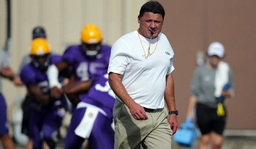 In this Aug. 23, 2017 photo, LSU football head coach Ed Oregon walks across the field during an NCAA college football practice in Baton Rouge, La. Orgeron grew up an LSU fan in Cajun country along the Bayou Lafourche in Larose, Louisiana, where his mother still lives. The Tigers' coach is about to begin his first full season on the job after taking over for Les Miles during last season. His Louisiana and Cajun roots made him a popular choice to keep the job long term.(AP Photo/Gerald Herbert)