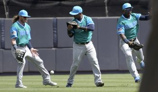 Seattle Mariners left fielder Ben Gamel, left, shortstop Jean Segura and center fielder Guillermo Heredia, right, converge on a single hit by New York Yankees' Gary Sanchez during the first inning of a baseball game Sunday, Aug. 27, 2017, at Yankee Stadium in New York. (AP Photo/Bill Kostroun)