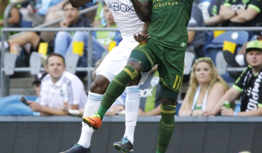 Seattle Sounders defender Kelvin Leerdam, left, and Portland Timbers forward Darren Mattocks, right, got up for a header in the first half of an MLS soccer match, Sunday, Aug. 27, 2017, in Seattle. (AP Photo/Ted S. Warren)