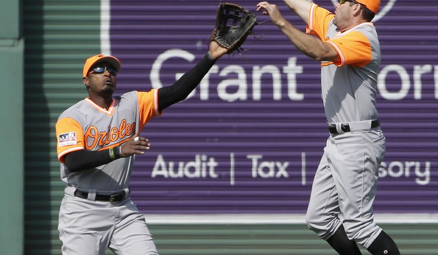 Baltimore Orioles' Seth Smith, right, leaps as he catches a fly ball by Boston Red Sox's Mookie Betts as Orioles' Adam Jones, left, backs him up in the fifth inning of a baseball game, Sunday, Aug. 27, 2017, in Boston. (AP Photo/Steven Senne)