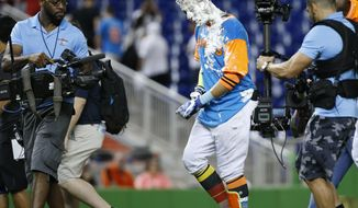 Miami Marlins' Miguel Rojas walks off the field covered in shaving cream after he was mobbed by teammates following his sacrifice fly that scored Derek Dietrich during the 11th inning of a baseball game against the San Diego Padres, Saturday, Aug. 26, 2017, in Miami. The Marlins defeated the Padres 2-1. (AP Photo/Wilfredo Lee)
