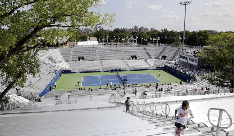 Children climb the bleachers at the temporary Louis Armstrong Stadium at the U.S. Open tennis tournament on Sunday, Aug. 27, 2017, in New York. The temporary stadium will be used while a new Louis Armstrong Stadium is built. Competition in the tournament starts on Monday. (AP Photo Peter Morgan)