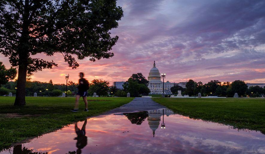 A pedestrian walks past a reflection of the U.S. Capitol in rain puddle at daybreak in Washington, Sunday, Aug. 13, 2017. (AP Photo/J. David Ake)