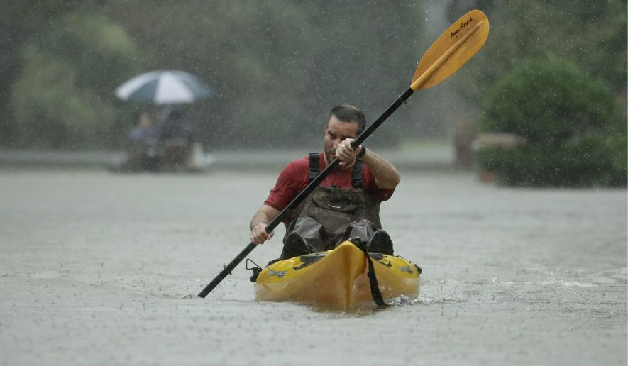 People evacuate a neighborhood in west Houston inundated by floodwaters. (Associated Press)